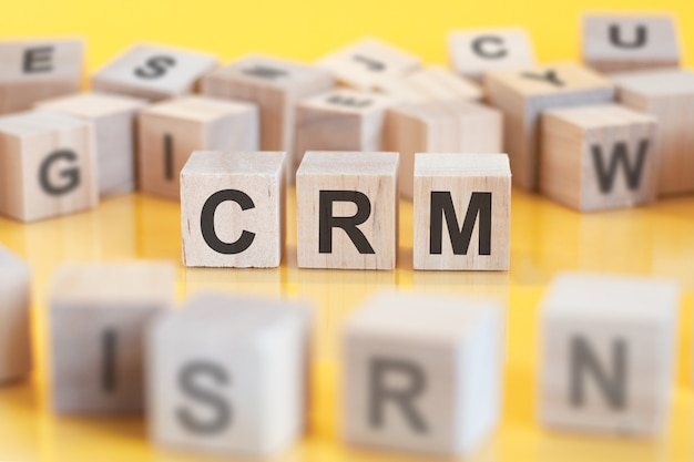 The word crm is written on a wooden cubes structure. blocks on a bright background. financial concept. selective focus. crm - shotr for customer relationship management