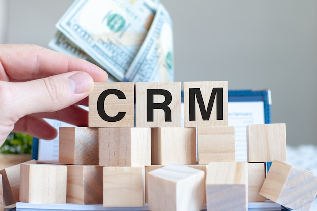 The word crm on wooden blocks and and dollar notes