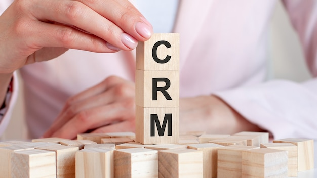 The word crm on a wooden toy blocks with womans hands, pink surface