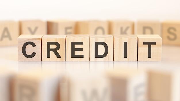단어 크레딧은 연속으로 서 있는 나무 큐브에 기록됩니다. 밝은 배경에 글자가 있는 블록 주위. 비즈니스 및 금융 개념에 사용할 수 있습니다. 선택적 초점