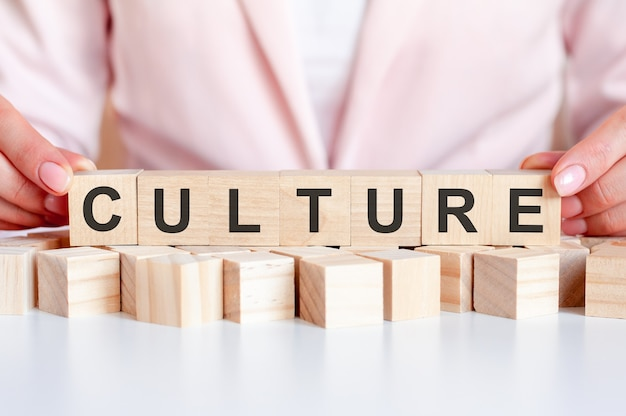 Word culture is written on wooden cubes standing on the white surface of the table on the pink background
