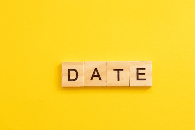 Word date made from wooden letters on yellow background.