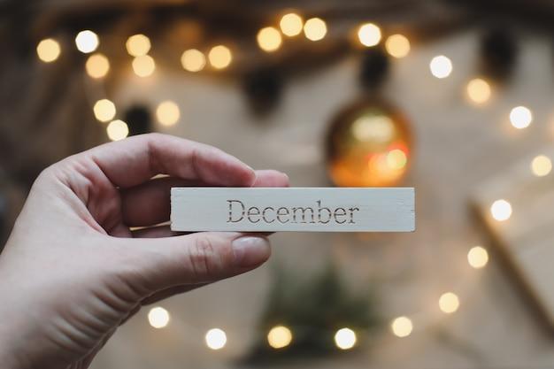 トウヒの枝と輝く花輪の背景でカレンダーの12月の言葉。クリスマス、冬、新年のコンセプト