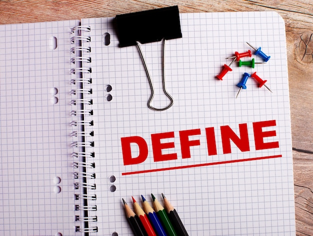 The word define is written in a notebook near multi-colored pencils and buttons on a wooden surface.
