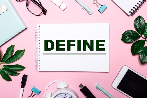 The word define is written in a white notebook on a pink background surrounded by business accessories and green leaves.