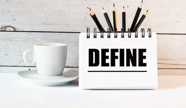 The word define is written in a white notepad near a white cup of coffee on a light background