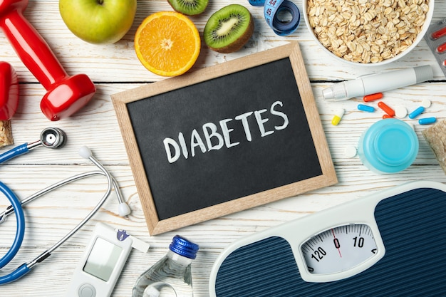 Word diabetes and diabetic accessories on wooden table