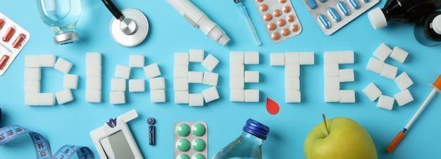 Слово диабет из кубиков сахара на синем фоне. аксессуары для диабета