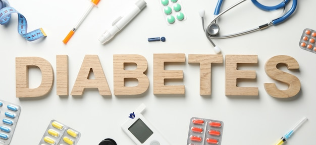 Слово диабет из деревянных букв на белом фоне. аксессуары для диабета