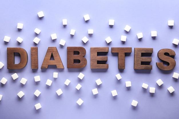 Слово диабет с кубиками сахара на цвете
