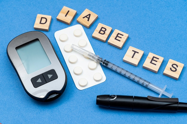 Word diabetes with syringe, pills, device for measuring blood sugar.