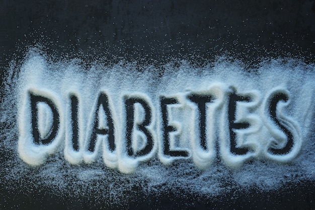 Word diabetes written on a pile of granulated sugar