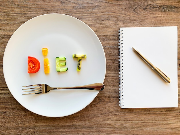 Word diet made of sliced vegetables in white plate and diet plan on wood