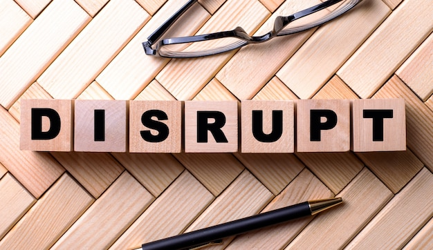 The word disrupt is written on wooden cubes on a wooden background next to a pen and glasses