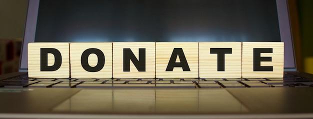 Слово пожертвовать. деревянные кубики с буквами, изолированные на клавиатуре ноутбука. изображение бизнес-концепции.