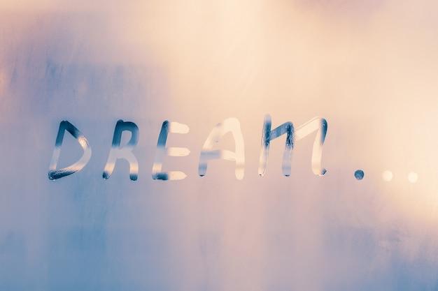 Word  dream... handwritten text on foggy window.
