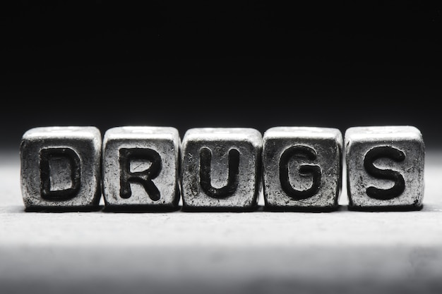 The word drugs on metal cubes on a black background