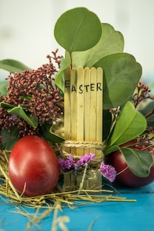 The word easter in the conceptual block text on wooden sticks, beautiful festive eggs with greens