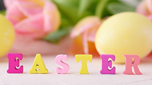 単語イースターは、花とイースターエッグの背景に色とりどりの文字、選択的な焦点、幸せなイースターの概念で構成されています