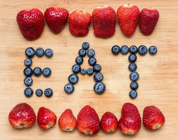 Word eat formed with blueberries with strawberries on wooden.