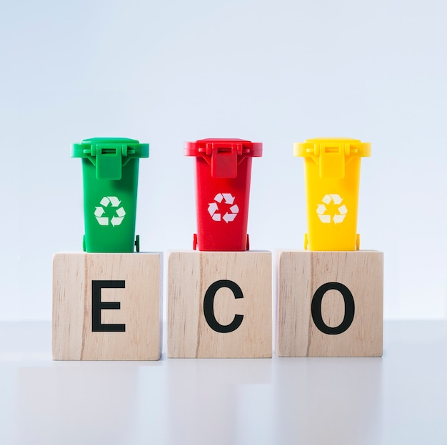 Word eco written onto a wooden cube and garbage cans. recycling concept.