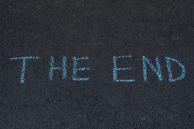 Word the end is written in chalk on the asphalt. inscription on pavement.