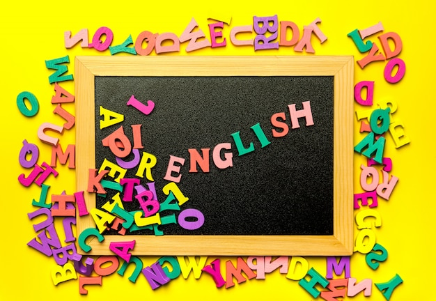 Word english made with wooden letters over the wooden board