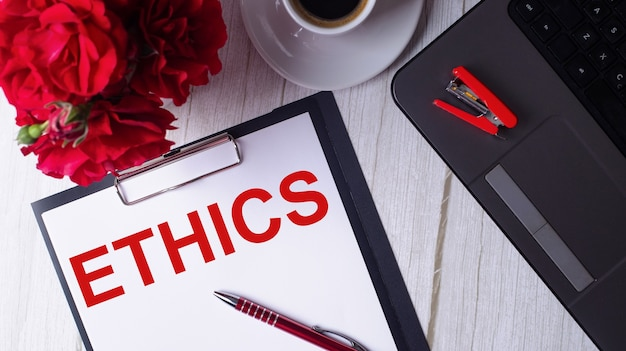 The word ethics is written in red on a white notepad near a laptop, coffee, red roses and a pen.