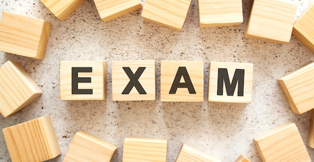 The word exam consists of wooden cubes with letters, top view on a light background. work space.
