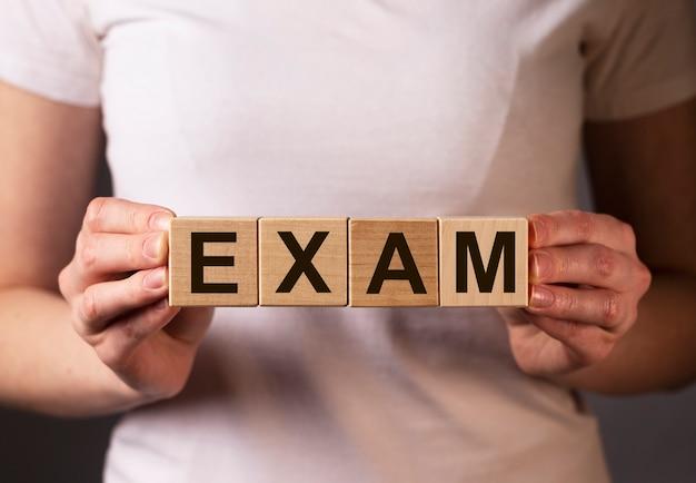 여성의 손에 나무 조각에 단어 시험.