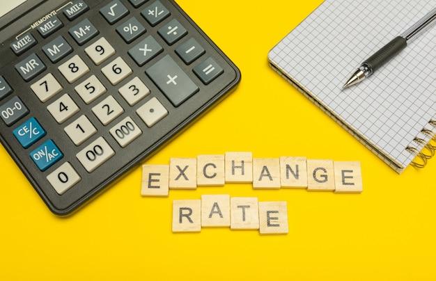 Курс обмена слов с деревянными буквами на желтом и современный калькулятор с ручкой и блокнотом. скопируйте пространство. экономика, денежное планирование. бизнес, концепция финансов. налоги и налогообложение.