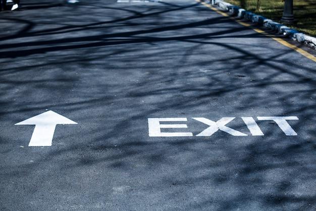 흰색 페인트로 쓰여진 도로의 단어 출구는 사람들에게 주차 도로 표지판을 따라갈 곳을 보여줍니다.