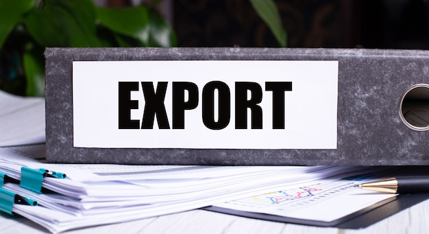 The word export is written on a gray file folder next to documents. business concept