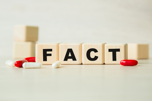 The word fact is written on a wooden cubes structure with tablets.