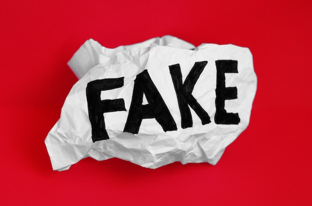 The word fake on crumpled paper on a red background