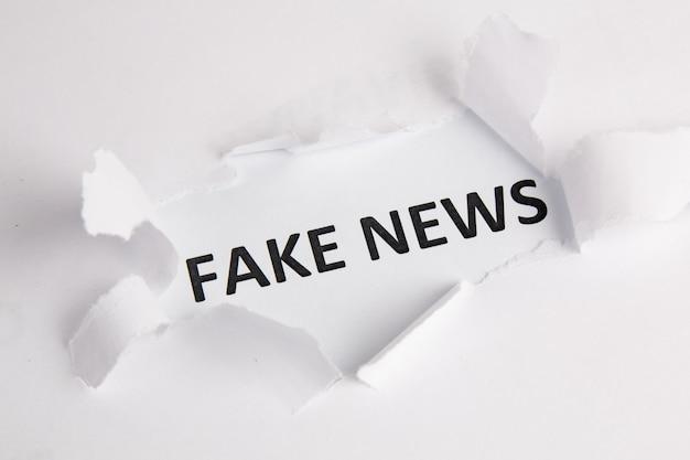 Word fake news written under torn white paper