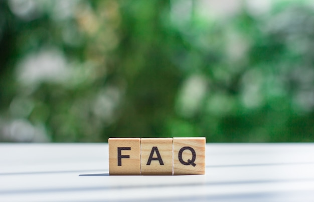 Word  faq message sign of wooden cubes on a light table against a background of green leaves in soft focus frequently asked question concept