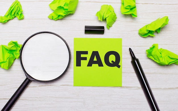 The word faq written on a green sticky note next to a magnifying glass and a black marker on a wooden table