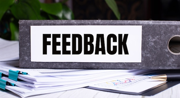 The word feedback is written on a gray file folder next to documents