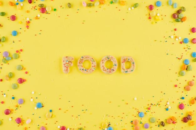 노란색 배경에 수제 설탕 쿠키에서 배열 된 단어 음식 wih 뿌리와 사탕