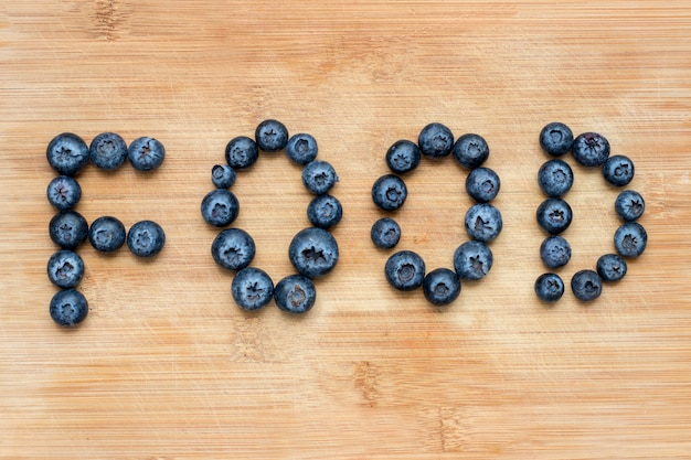 Word food formed with blueberries on wooden