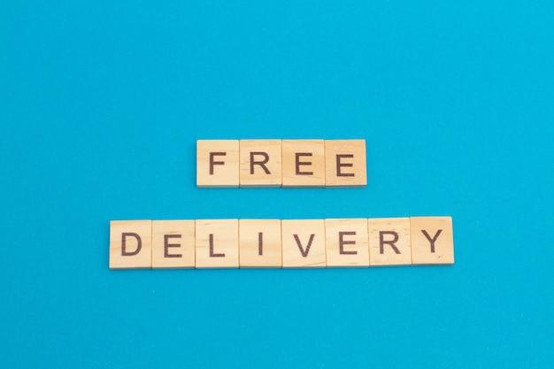 파란색 배경에 나무 큐브로 만든 단어 무료 배송