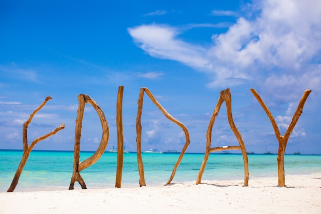 Word friday made of wood on boracay island background turquoise sea