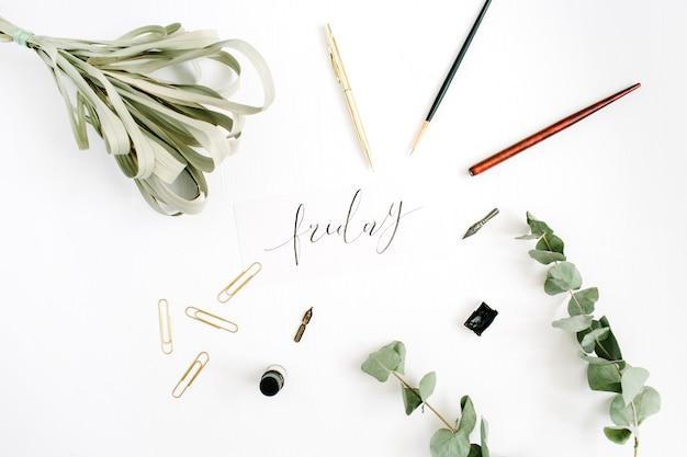펜, 브러시, 유칼립투스 및 클립이있는 흰색에 서예로 작성된 금요일 단어