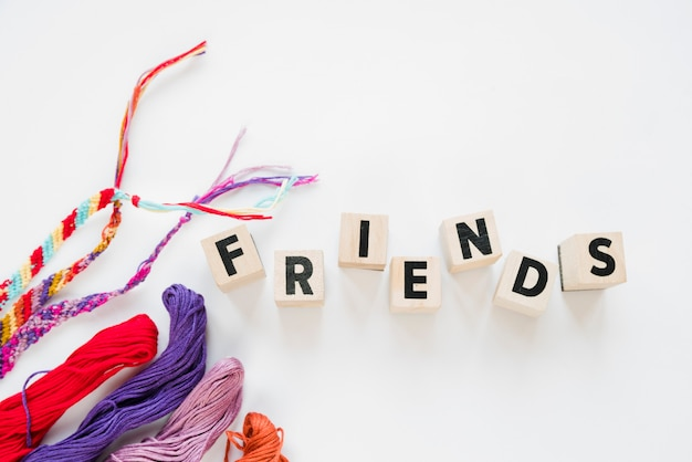 Word friends on wooden blocks and colorful threads