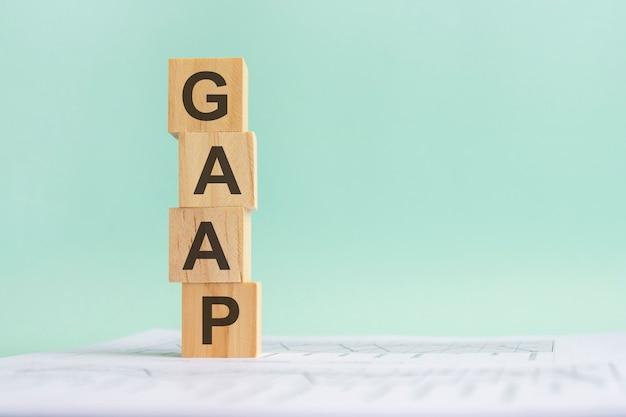 Слово gaap с деревянными строительными блоками, голубой фон. документ с числами на фоне, бизнес-концепция. место для текста справа. передний план