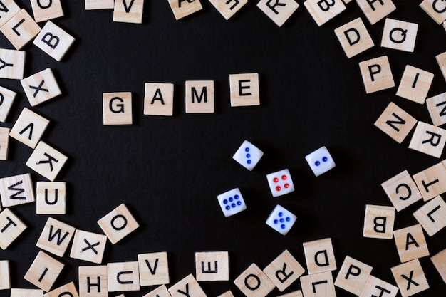 Word game with wooden letters on black board with dice and letter in the circle