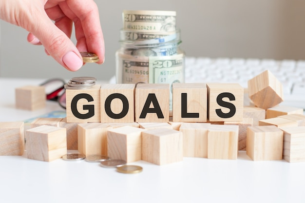 The word goals on the wooden blocks and a bank with money in the wall, business concept
