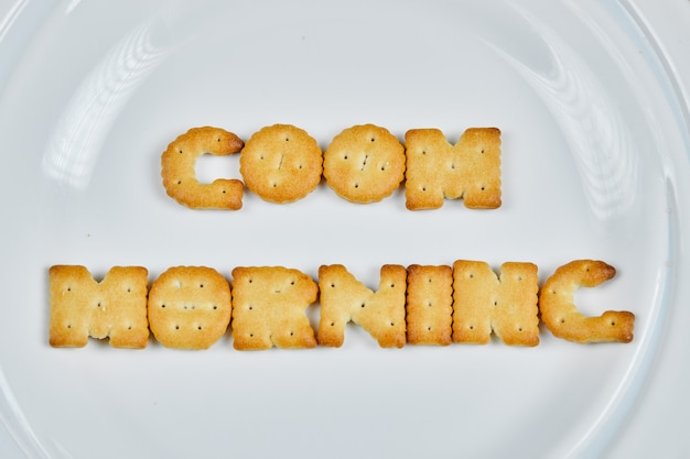 Word good morning spelled with crackers on a white plate.