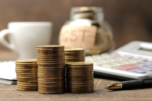 The word gst in the background and a stack of coins with a calculator pen and coffee on a brown wooden background.